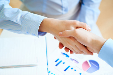Close-up of female and male handshaking over workplace with business documents