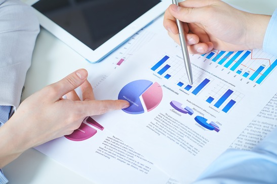 Close-up of female and male hands pointing at paper with financial data